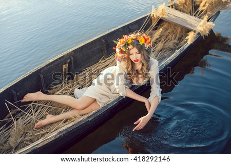 Young sexy woman on boat at sunset. The girl has a flower wreath on her head, relaxing and sailing on river. Beautiful body and face. Fantasy art photography. Concept of female beauty, rest in the - stock photo