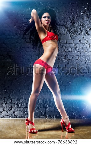 Young sexy woman on brick wall background. - stock photo