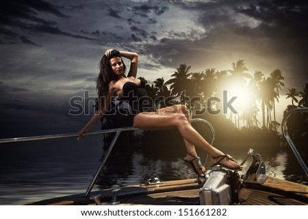 Young sexy woman on her private yacht at sunset around tropical island - stock photo