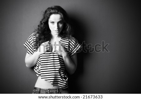 Young sexy woman on wall background. Black and white. - stock photo