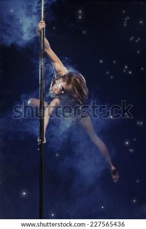 Young sexy woman pole dancer. Smoke and stars studio photo  - stock photo