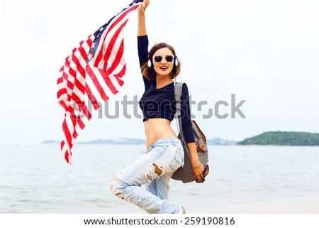 Young sexy woman posing at the beach listening music in her stylish big headphones, dancing and singing, travel with backpack, holding american flag.  Positive crazy mood. - stock photo