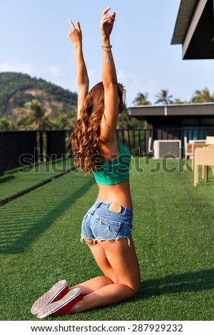 Young sexy woman, posing back to camera, dancing and having fun on roof summer party, have perfect fit body butt and legs, trendy hipster swag outfit. - stock photo