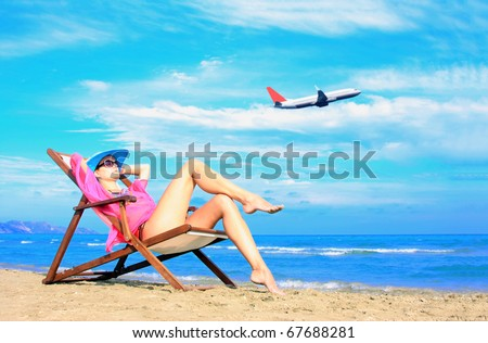 Young sexy woman Relaxing on the beach with an airplane passing behind her - Travel concept - stock photo