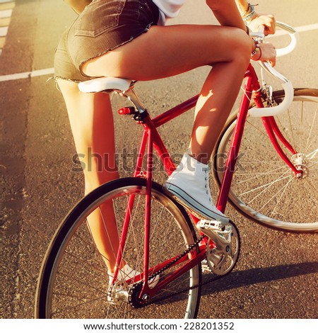 Young sexy woman sexy back on sport style red fixed gear bicycle posing on the road and have fun in hot summer  - stock photo