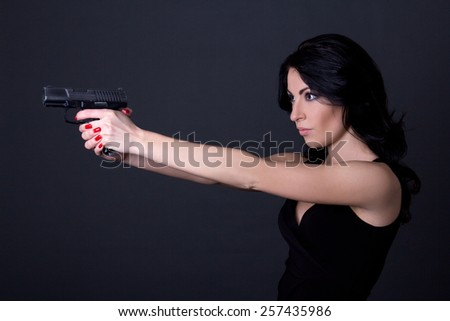 young sexy woman shooting with gun over grey background - stock photo