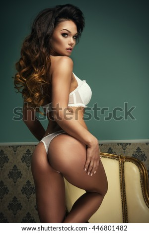 Young sexy woman sitting on chair.   - stock photo