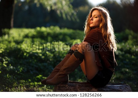 young sexy woman sitting on log posing