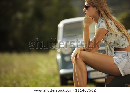 Young sexy woman sitting on suitcases at the roadside, vintage cars in the background - stock photo