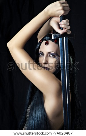 Young sexy woman warrior holding sword in hands with long healthy black hair. - stock photo