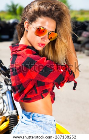 Young sexy woman,wear denim summer outfit and holding mirrored sunglasses,perfect glowing tan skin,attractive,joy and happiness,trim,athletic figure,perfect female body,Motorcycles and drift show - stock photo