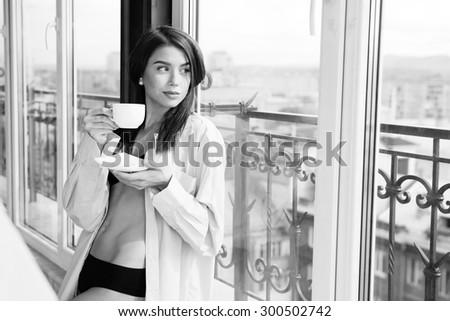 Young sexy woman wearing man's shirt and enjoying her morning coffee - stock photo