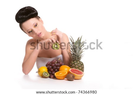 Young, sexy woman with a lot of tasty, fresh, healthy fruits. Holding heart-shaped kiwi in her hand. On white isolated, a lot of copyspace available. - stock photo