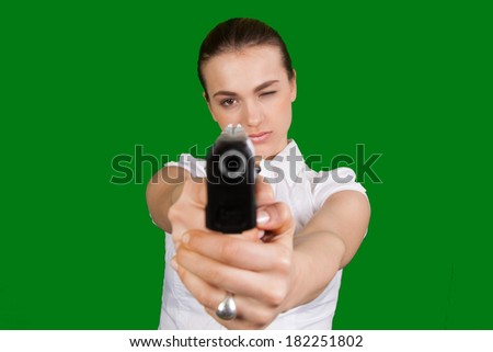 Young sexy woman with gun isolated on Green - stock photo