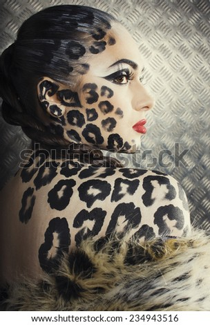 young sexy woman with leopard make up all over body, cat bodyart print closeup - stock photo