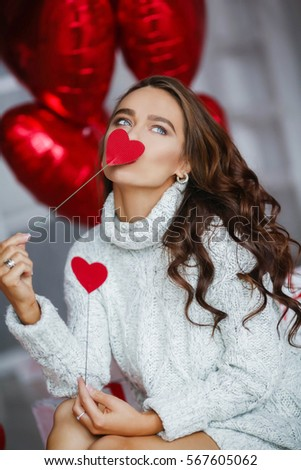 Young sexy woman with make-up and hairdo, with gifts and balloons