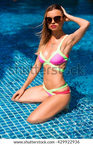 Young sexy woman with sport body in sunglasses and swimsuit is posing on the sun bed near the swimming pool - stock photo