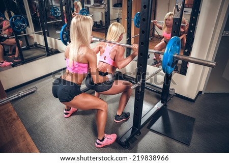Young sexy women in the gym doing squat with barbell - stock photo