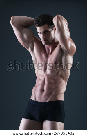 Young shirtless muscular man in black underwear with hands behind his head - stock photo