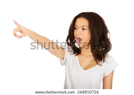 Young shocked african woman pointing up.