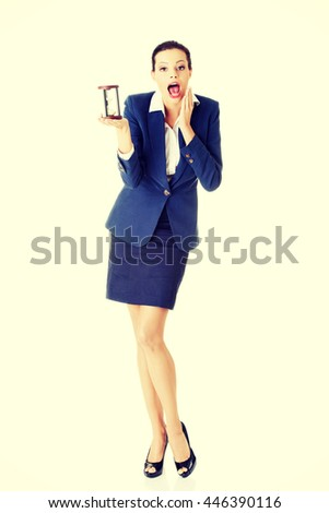 Young shocked business woman with hourglass