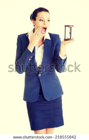 Young shocked business woman with hourglass - time concept - stock photo