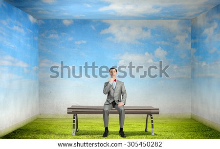 Young shocked businessman sitting on wooden bench