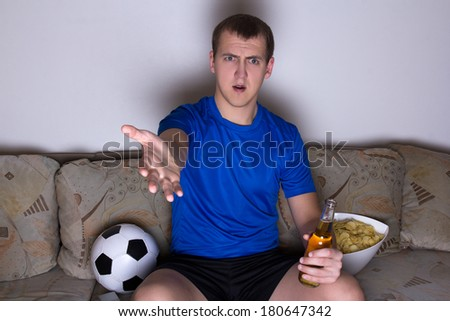 young shocked emotional supporter in uniform sitting on the sofa and watching soccer with beer and chips - stock photo