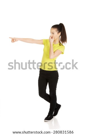 Young shocked student woman pointing aside. - stock photo