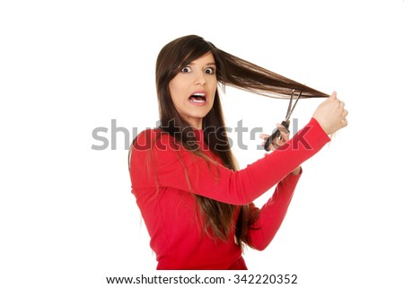Young shocked woman cutting her hair. - stock photo