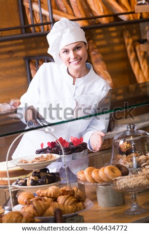 Young shop girl offering with delicious chocolate and confectionery at display
