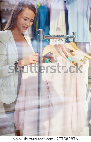 Young shopper looking through new clothes - stock photo