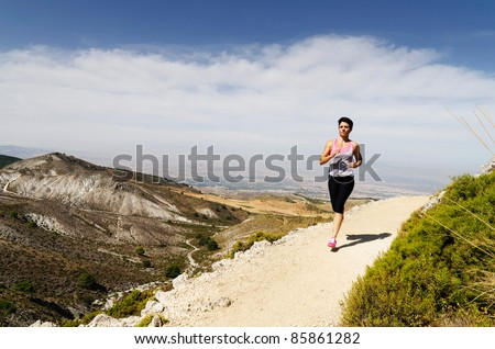 Young short-haired woman  running on a dry mountain path. - stock photo