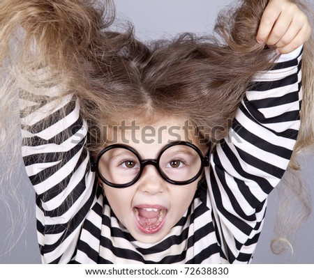 Young shouting child in glasses and striped knitted jacket. Studio shot. - stock photo