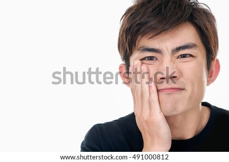 Young shy man with hand over his face