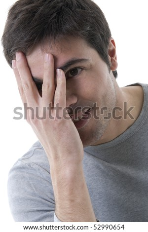 Young shy man with hand over his face - stock photo