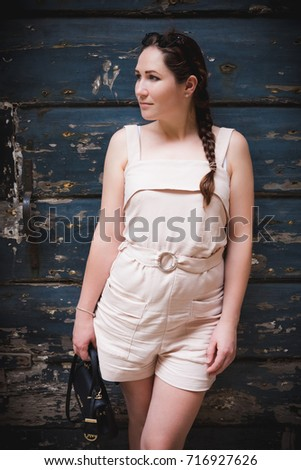Young shy ukraine girl in short beige summer dress posing in front of dark blue wooden wall.