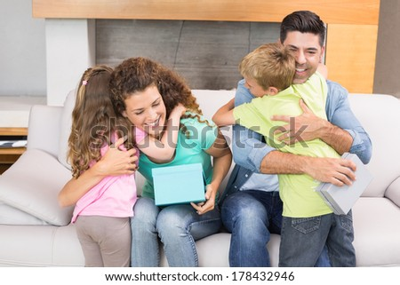 Young siblings giving presents to their parents at home in living room - stock photo