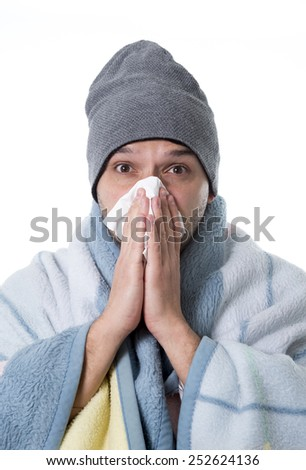 young sick and ill man in bed holding tissue cleaning snotty nose having temperature feeling bad infected by winter grippe virus in flu and influenza health care concept - stock photo