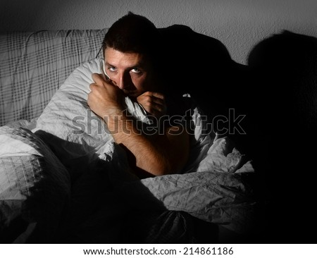 young sick looking man sitting on couch at home scary desperate looking, suffering insomnia, depression, nightmares, emotional crisis or mental disorder with dim light and deep dark shadow on the wall - stock photo