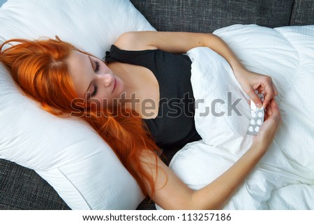 Young sick woman lying in bed and holding pills - stock photo