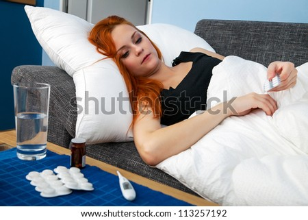 Young sick woman lying in bed holding pills - stock photo