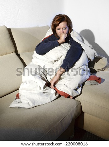 young sick woman sitting on couch wrapped in duvet and blanket feeling miserable and ill couching and suffering a cold at home - stock photo