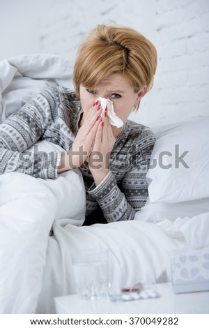 young sick woman with sneezing nose blowing in tissue lying on bed suffering winter cold and flu virus symptoms having medicines tablets and pills in illness and domestic health care concept