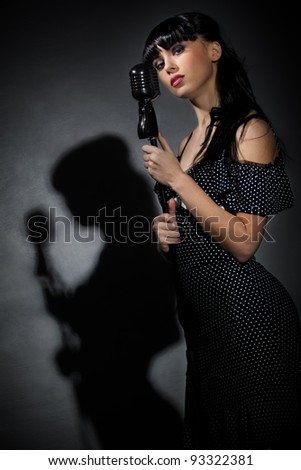 Young Singer with microphone in back light - stock photo