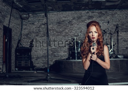 Young singer woman with red hair on the scene