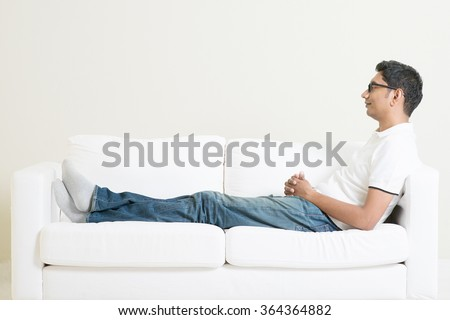 Young single Indian guy daydreaming and rest at home. Asian man relaxed on sofa indoor. Handsome male model. - stock photo