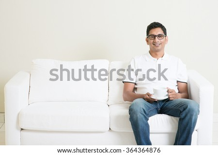 Young single Indian guy sitting on sofa alone and drinking coffee, copy space at side. Lifestyle Asian man at home. Handsome male model. - stock photo