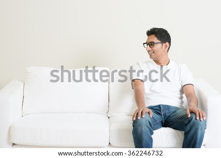 Young single Indian guy sitting on sofa alone and looking at side copy space. Lifestyle Asian man at home. Handsome male model. - stock photo