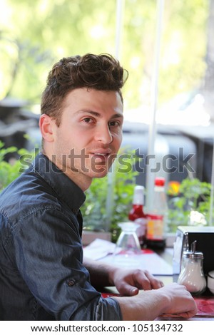 Young single man in restaurant waiting to be served